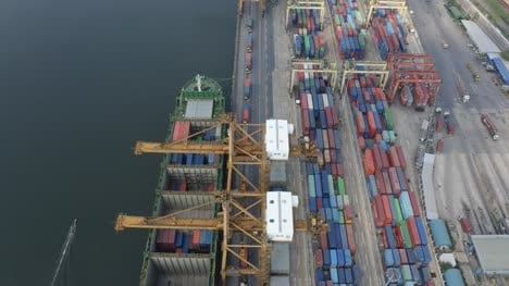 Small-Boat-Sailing-Past-Container-Port